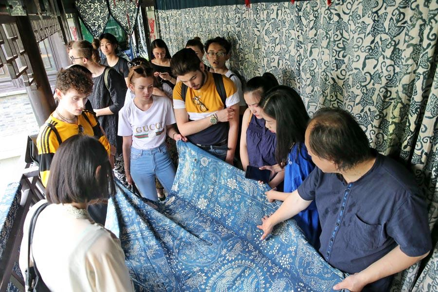 Chinese and British students from the China Academy of Art\'s creative fashion design camp listen to explanations of patterns on traditional Chinese blue calico in Nantong, East China\'s Jiangsu Province, on July 3, 2018. This year\'s camp features students from eight British universities including Southampton\'s Solent University and Edinburgh University, as well as others from Shanghai Institute of Design of the China Academy of Art. (Photo/Asianewsphoto)