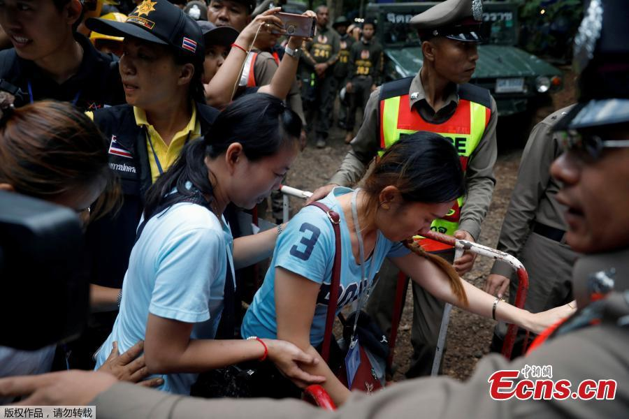 Family members are escorted by police on their way to enter the Tham Luang cave complex, as members of an under-16 soccer team and their coach have been found alive according to local media, in the northern province of Chiang Rai, Thailand, July 4, 2018. (Photo/Agencies)