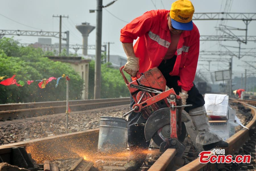 A worker races against time to repair the tracks on the Beijing-Kowloon railway in Gongqingcheng City, Jiangxi Province, July 4, 2018, after temperatures reached 30 degrees centigrade. The maintenance work had to be completed in two hours to minimize impact on the busy railway line. (Photo: China News Service/Wang Hao)