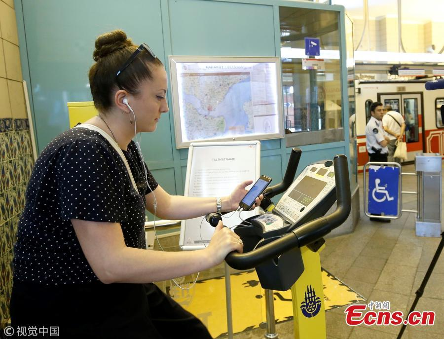 A woman uses a bicycle pedal power generator which was installed by the IETT (Istanbul electric tramway and tunnel establishments) at the Tunnel railway station to charge her mobile phone in Istanbul, Turkey, July 05, 2018. (Photo/Agencies)