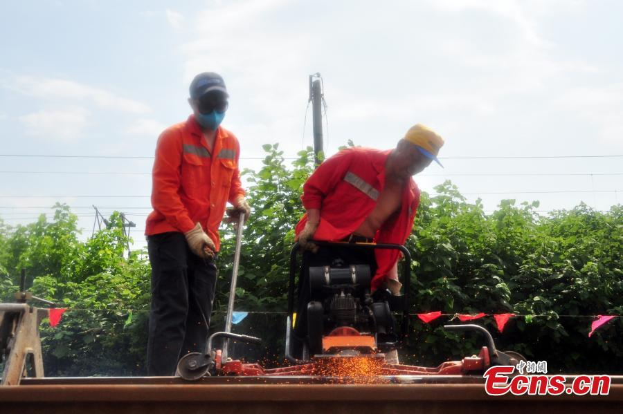 Workers race against time to repair the tracks on the Beijing-Kowloon railway in Gongqingcheng City, Jiangxi Province, July 4, 2018, after temperatures reached 30 degrees centigrade. The maintenance work had to be completed in two hours to minimize impact on the busy railway line. (Photo: China News Service/Wang Hao)