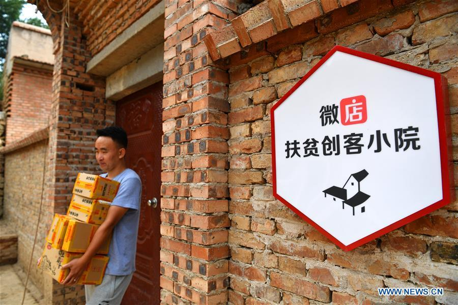 A deliveryman carries packages at a delivery post in Lingtou Village of Wuxiang County, north China\'s Shanxi Province, July 3, 2018. Online business helped villagers sell their farm products, significantly increasing the average incomes of local residents in Lingtou Village. (Xinhua/Zhan Yan)
