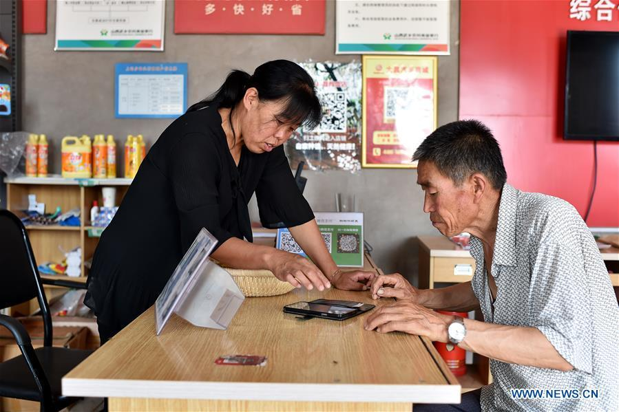Zhang Xiaoying (L) teaches Zhang Guocheng how to start an online business on cellphone in Lingtou Village of Wuxiang County, north China\'s Shanxi Province, July 5, 2018. Online business helped villagers sell their farm products, significantly increasing the average incomes of local residents in Lingtou Village. (Xinhua/Zhan Yan)