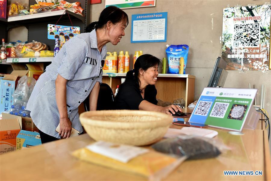 Zhang Xiaoying and Li Runhong exchange ideas about their online business in Lingtou Village of Wuxiang County, north China\'s Shanxi Province, July 5, 2018. Online business helped villagers sell their farm products, significantly increasing the average incomes of local residents in Lingtou Village. (Xinhua/Zhan Yan)