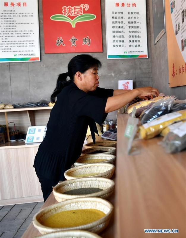 Zhang Xiaoying sorts out goods in Lingtou Village of Wuxiang County, north China\'s Shanxi Province, July 5, 2018. Online business helped villagers sell their farm products, significantly increasing the average incomes of local residents in Lingtou Village. (Xinhua/Zhan Yan)