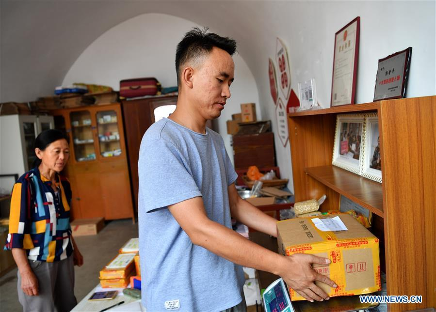 A deliveryman weighs the package at a delivery post in Lingtou Village of Wuxiang County, north China\'s Shanxi Province, July 3, 2018. Online business helped villagers sell their farm products, significantly increasing the average incomes of local residents in Lingtou Village. (Xinhua/Zhan Yan)