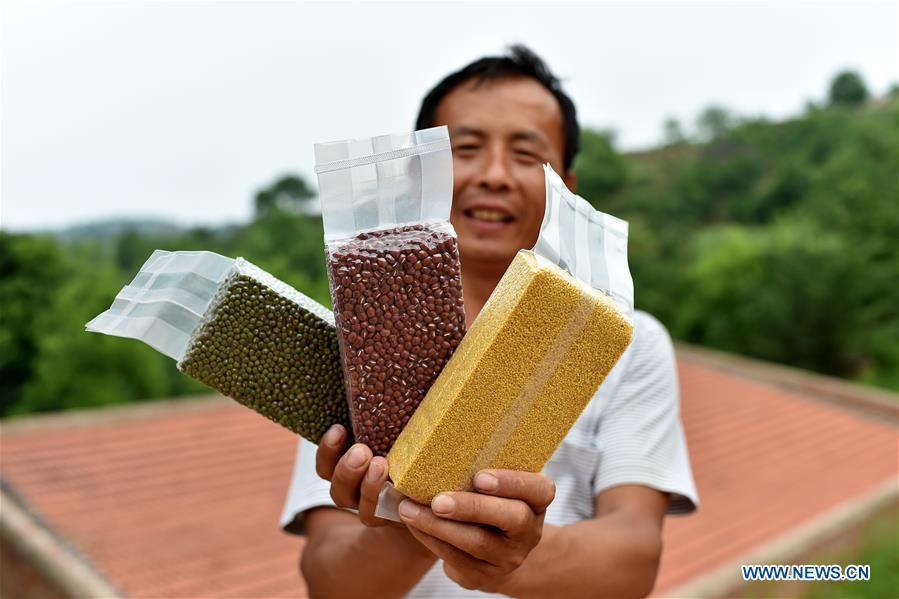 Wei Baoyu presents his products in Lingtou Village of Wuxiang County, north China\'s Shanxi Province, July 3, 2018. Online business helped villagers sell their farm products, significantly increasing the average incomes of local residents in Lingtou Village. (Xinhua/Zhan Yan)