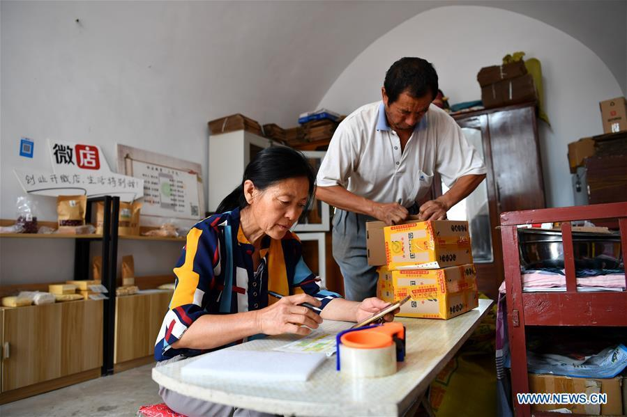 Guo Jinping (L) fills in the waybill while her husband Wei Guo packs the goods in Lingtou Village of Wuxiang County, north China\'s Shanxi Province, July 3, 2018. Online business helped villagers sell their farm products, significantly increasing the average incomes of local residents in Lingtou Village. (Xinhua/Zhan Yan)