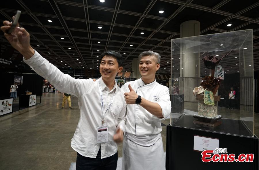 Chef Li Shaohui (R) poses with his chocolate creation at the first Salon du Chocolat at the Hong Kong Convention and Exhibition Center, July 6, 2018. Salon du Chocolat, one of the world's biggest chocolate events, showcases chocolate sculptures inspired by Hong Kong culture and the Year of the Dog. Meanwhile, guests were also able to sample award-winning creations during a live pastry show. (Photo: China News Service/Zhang Wei)