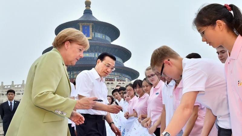 Premier Li and Chancellor Merkel sign on a memorial banner when meeting with youngsters attending the closing ceremony of the \