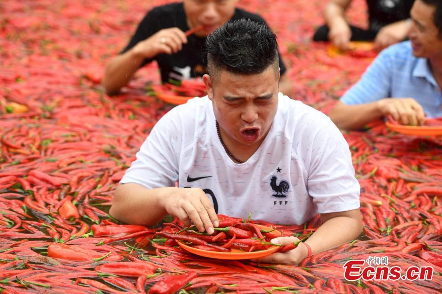 A participant chews chili peppers in a contest in Ningxiang City, Central China's Hunan Province, July 8, 2018. Tang Shuaihui, a local resident, swallowed 50 chili peppers in one minute to win first prize. (Photo: China News Service/Yang Huafeng)
