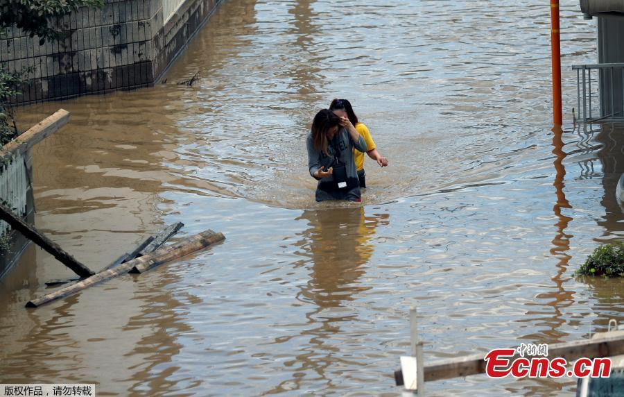 Women make their way through a flooded area in Mabi town in Kurashiki, Okayama Prefecture, Japan, July 8, 2018. The death toll from torrential rain and landslides in western Japan rose to 88 people early on Monday, with dozens still missing after the rescue of more than 2,000 stranded in the city of Kurashiki.(Photo/Agencies)