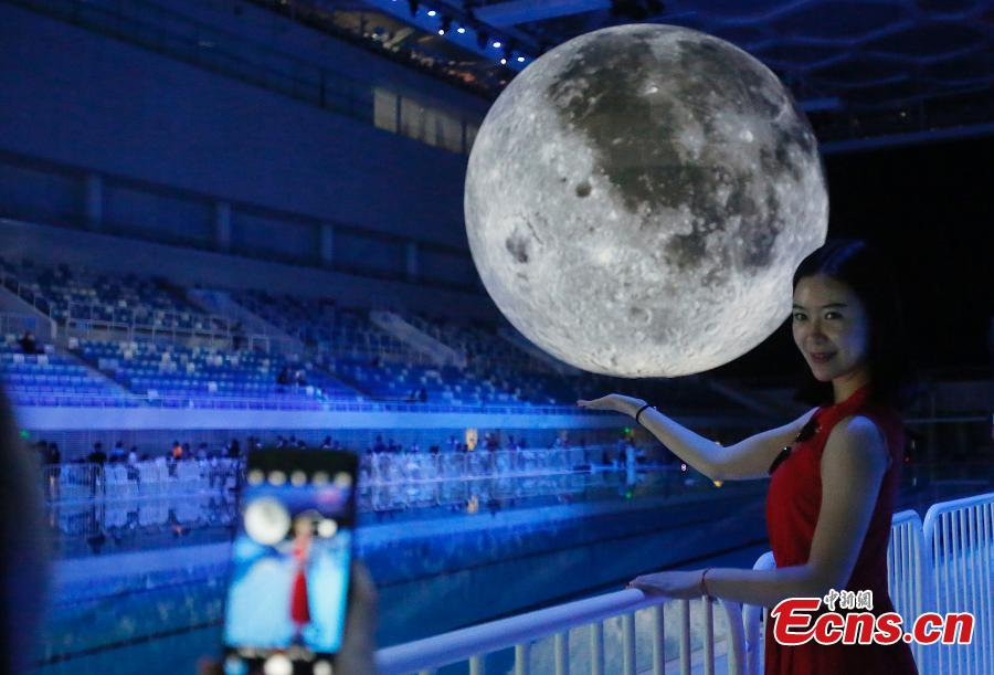 Visitors take photos of a huge moon model during an exhibition on moon held at the National Aquatic Center or \
