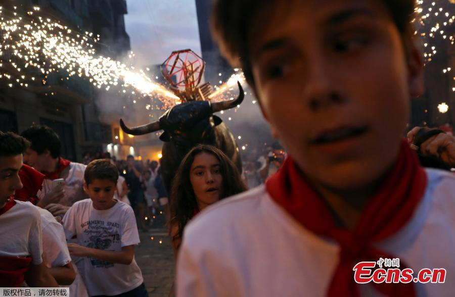 Revelers run from the Fire Bull, a man carrying a bull figure packed with fireworks, at the San Fermin festival in Pamplona, Spain July 8, 2018. (Photo/Agencies)