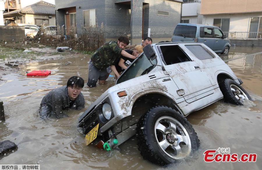 Residents try to upright a vehicle stuck in a flood hit area in Kurashiki, Okayama prefecture on July 9, 2018. The death toll from widespread flooding and landslides rose to 126, according to Japanese authorities. (Photo/Agencies)