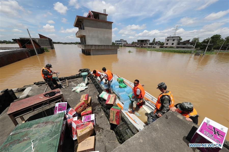 Rescue workers transport relief supplies in Dongxiang Disctrict of Fuzhou City, east China\'s Jiangxi Province, July 8, 2018. Flood caused by heavy rain damaged crops and housings in Maxu Township of Dongxiang and rescue groups were set up to help the affected people. (Xinhua/He Jianghua)