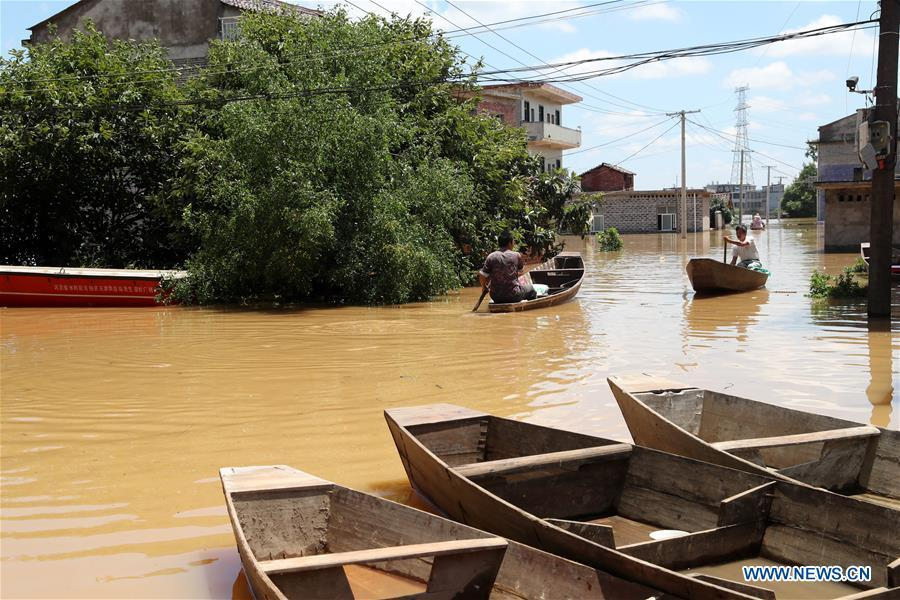 Residents take boat in flooded area in Qiaoxi Village of Maxu Township of Fuzhou City, east China\'s Jiangxi Province, July 8, 2018. Flood caused by heavy rain damaged crops and housings in Maxu Township and rescue groups were set up to help the affected people. (Xinhua/He Jianghua)