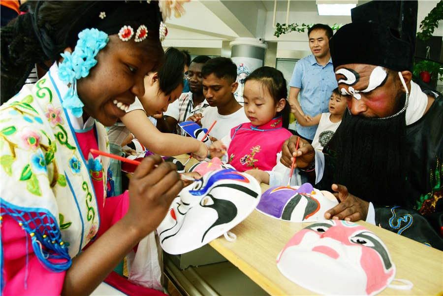 Foreign students paint Peking Opera masks with children in Zhenjiang city, Jiangsu Province, on July 9, 2018.  (Photo/Asianewsphoto)