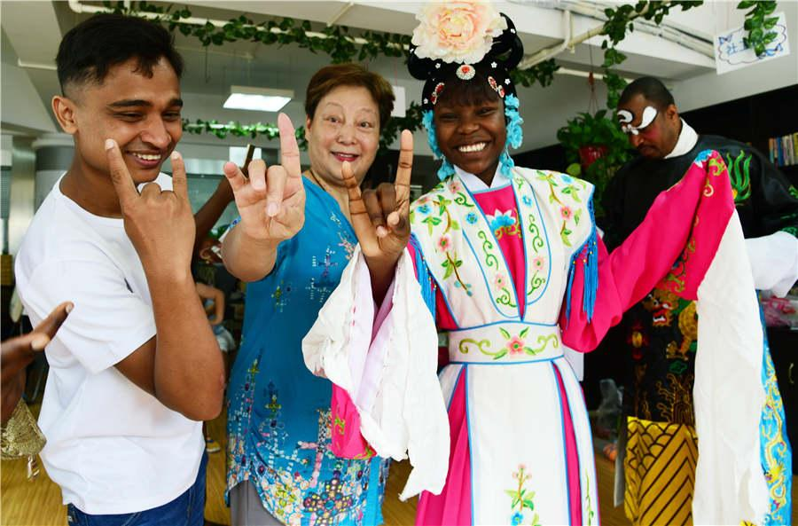 A teacher guides foreign students to learn movement from Peking Opera in Zhenjiang city, Jiangsu Province, on July 9, 2018. (Photo/Asianewsphoto)