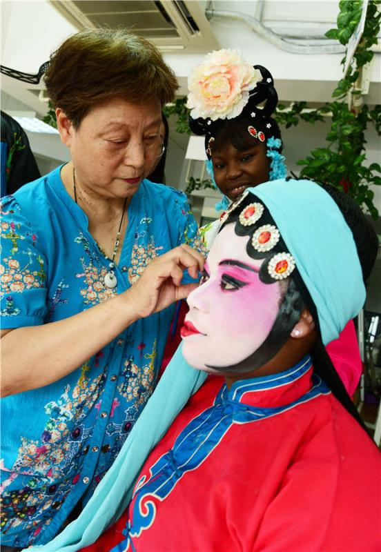 A teacher applies facial makeup to a foreign student in Zhenjiang city, Jiangsu Province, on July 9, 2018.  (Photo/Asianewsphoto)