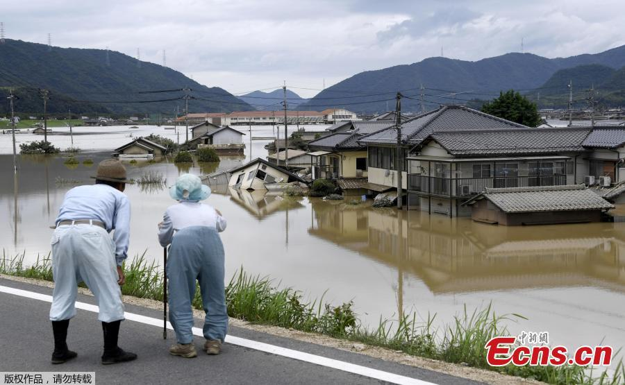 An elderly couple looks at a flooded area after heavy rain in Kurashiki, Okayama Prefecture, Japan, in this photo taken by Kyodo July 8, 2018. The death toll from widespread flooding and landslides rose to 126, according to Japanese authorities.  (Photo/Agencies)