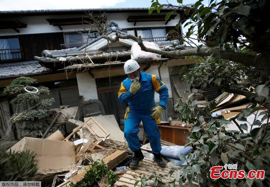A police officer checks a submerged and destroyed house in a flood affected area in Mabi town in Kurashiki, Okayama Prefecture, Japan, July 10, 2018.The death toll from widespread flooding and landslides rose to 126, according to Japanese authorities.  (Photo/Agencies)