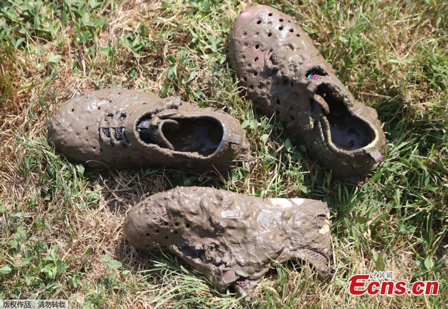 Mud caked shoes are seen next to the giant 75\' x 150\' mud pit at the Nankin Mills Park, July 10, 2018, in Westland, Mich. The event marked the 31st year Wayne County Parks has hosted Mud Day. While much of the event was children and parents playing in the mud, park officials organized various races and a limbo line. (Photo/Agencies)