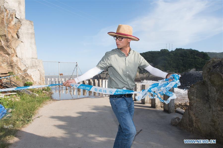 A staff member lines up cordon tape for precaution at a harbor in Xiaguan Town of Cangnan County, east China\'s Zhejiang Province, July 10, 2018, as Typhoon Maria, the eighth typhoon this year, approaches the Chinese coast. (Xinhua/Weng Xinyang)
