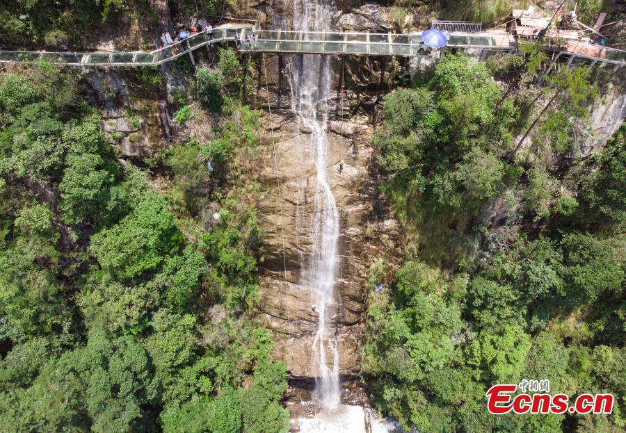 Two adventurers abseil down a 106-meter-high waterfall in Jiulong River National Park in Rucheng County, Central China's Hunan Province, July 10, 2018. Two participants took five minutes to descend a rope from a glass walkway at the top of a cliff to the ground below. (Photo: China News Service/Yang Huafeng)