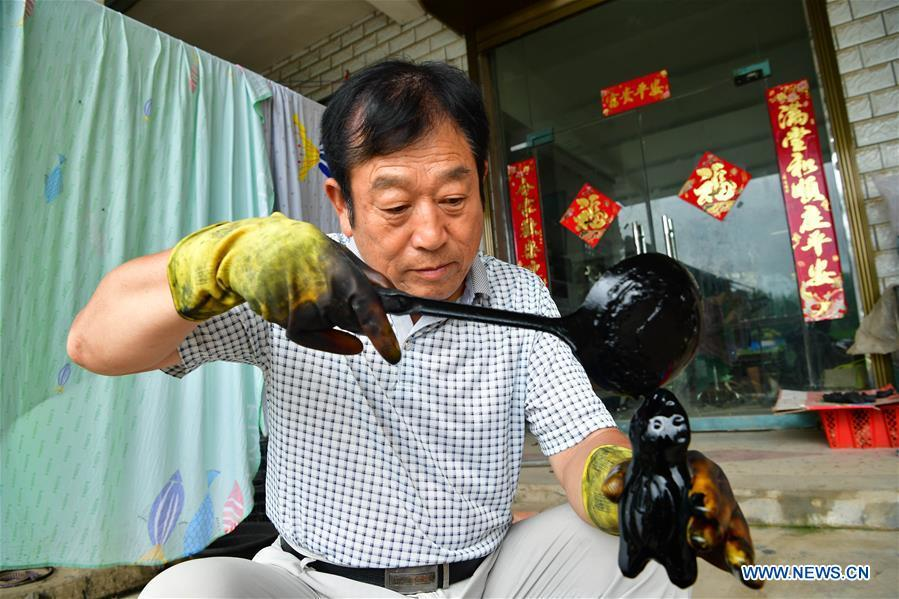 Local handicraftsman Ren Guohe colours a clay statuette in Jinzhuang Village of Huaiyang County, central China\'s Henan Province, July 9, 2018. Originated from ancient sacrificial ceremonies, the hand-made clay statuette \