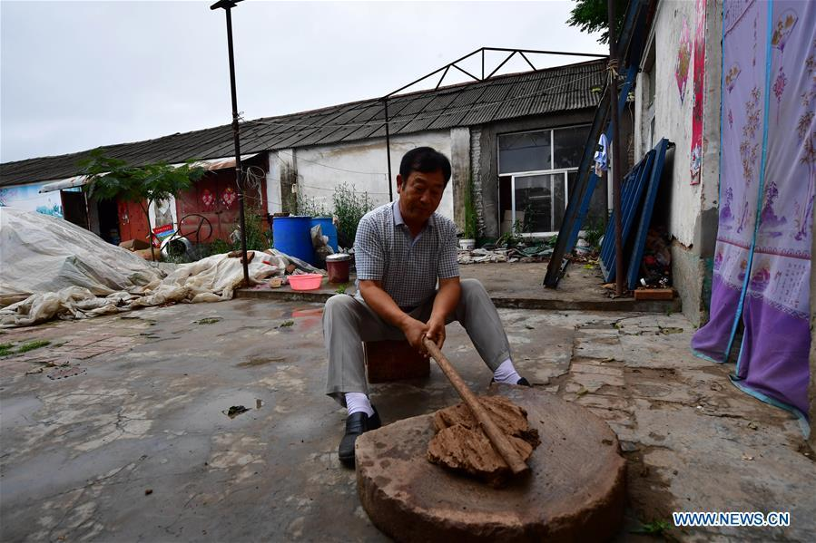 Local handicraftsman Ren Guohe prepares materials for making clay statuettes in Jinzhuang Village of Huaiyang County, central China\'s Henan Province, July 9, 2018. Originated from ancient sacrificial ceremonies, the hand-made clay statuette \