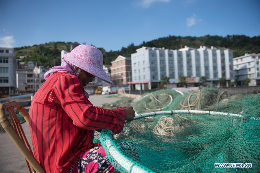 A fisherman mends fishing nets at a harbor in Xiaguan Town of Cangnan County, east China\'s Zhejiang Province, July 10, 2018, as Typhoon Maria, the eighth typhoon this year, approaches the Chinese coast. (Xinhua/Weng Xinyang)