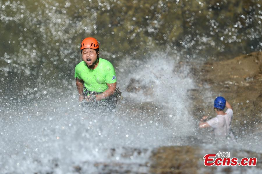 Ma Ming abseils down a 106-meter-high waterfall in Rucheng County, Central China's Hunan Province, July 10, 2018. Two participants took five minutes to descend a rope from a glass walkway at the top of a cliff to the ground below. (Photo: China News Service/Yang Huafeng)