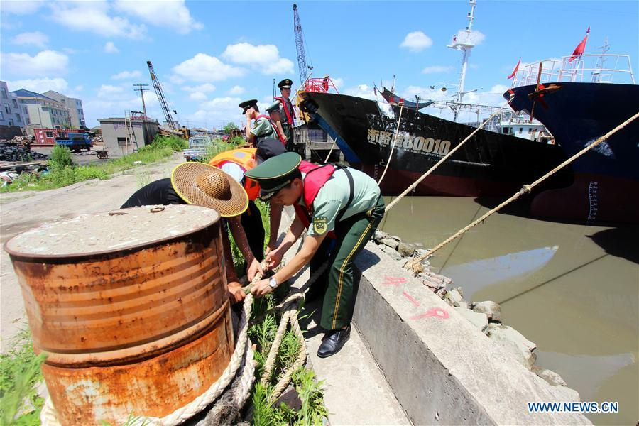 Police officers and soldiers help a fisherman moor fishing boats in Taizhou, east China\'s Zhejiang Province, July 10, 2018. China Meteorological Administration on Tuesday issued this year\'s first red alert for typhoon as the Typhoon Maria or the 8th of the year approaches the Chinese coast. Typhoon Maria is likely to sweep Taiwan, Fujian, Jiangxi and part of Zhejiang on Tuesday and Wednesday.(Xinhua/Jiang Youqin)