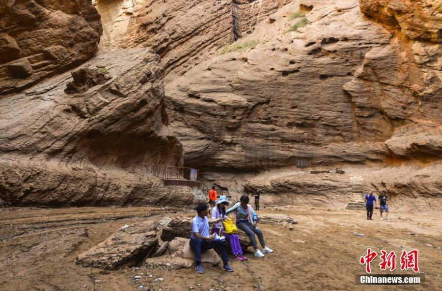 Visitors look at Kuqa Gorge, located to the south of Tianshan Mountain and about 60 kilometers to the north of Kuqa county in Aksu, Xinjiang Uygur Autonomous Region, July 10, 2018. Kuqa Gorge is made up of huge red mountains which are called \