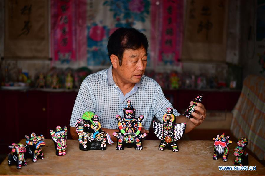 Local handicraftsman Ren Guohe displays clay statuettes in Jinzhuang Village of Huaiyang County, central China\'s Henan Province, July 9, 2018. Originated from ancient sacrificial ceremonies, the hand-made clay statuette \