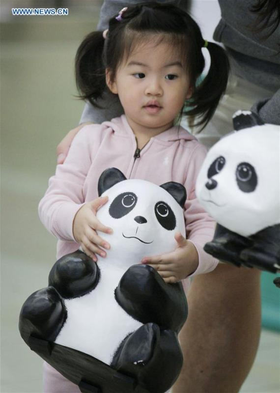 A girl plays with a papier-mache panda during an exhibition of the papier-mache artwork \