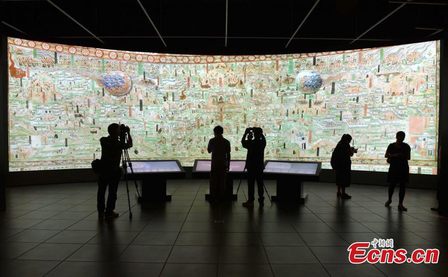 Visitors look at the Digital Dunhuang - Tales of Heaven and Earth exhibition at the Hong Kong Heritage Museum, July 10, 2018. Jointly presented by the Hong Kong Leisure and Cultural Services Department and the Dunhuang Academy, the exhibition highlights the achievements of digitization projects at the Dunhuang Academy, together with a presentation of unearthed artefacts, the grotto art of Dunhuang, and the latest multimedia technology. The Dunhuang Academy has made substantial achievements in digitization, 3D scanning and virtual reality representation of the Dunhuang relics. (Photo: China News Service/Zhang Wei)