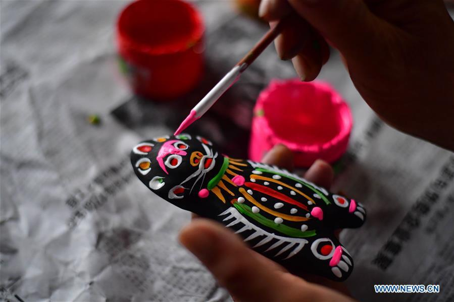 Local handicraftsman Ren Guohe paints on a clay statuette in Jinzhuang Village of Huaiyang County, central China\'s Henan Province, July 9, 2018. Originated from ancient sacrificial ceremonies, the hand-made clay statuette \
