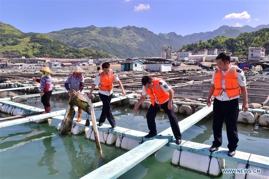 Staff members help villagers on precaution work in Cheng\'ao Village of Sanduao Town in Ningde City, southeast China\'s Fujian Province, July 10, 2018, as Typhoon Maria, the eighth typhoon this year, approaches the Chinese coast. China\'s National Meteorological Center (NMC) issued this year\'s first red alert for Typhoon Maria, which is expected to hit China\'s coastal provinces on Wednesday morning. (Xinhua/Lin Shanchuan)