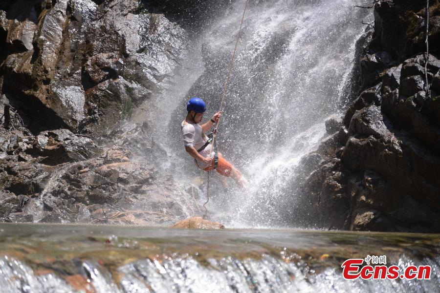 Sun Si abseils down a 106-meter-high waterfall in Jiulong River National Park in Rucheng County, Central China's Hunan Province, July 10, 2018. Two participants took five minutes to descend a rope from a glass walkway at the top of a cliff to the ground below. (Photo: China News Service/Yang Huafeng)
