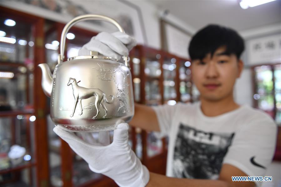 A worker displays a silverware at a workshop in Malanyu Township in Zunhua City, north China\'s Hebei Province, July 11, 2018. Gold and silver processing in Malanyu Township has a long history and the industry is expanding as craftsmen blend modern elements with traditional techniques in recent years. To date, there are more than 80 enterprises that provide over 2,000 jobs for local residents. (Xinhua/Mu Yu)