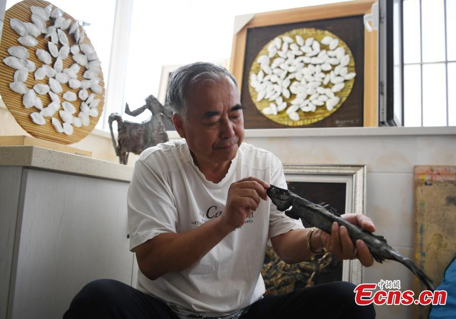 Sui Jincai, an art teacher, shows iron artworks in Changchun City, Jilin Province, July 11, 2018. Sui uses acrylic paints and iron materials to create vivid 3D creations. (Photo: China News Service/Zhang Yao)