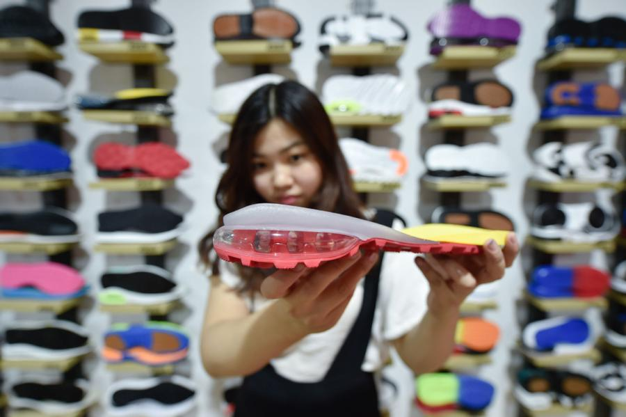 A saleswoman of a sole manufacturer displays an air-bag sole developed by the company in Jinjiang, Fujian Province, on April 20, 2017. (Photo/Xinhua)