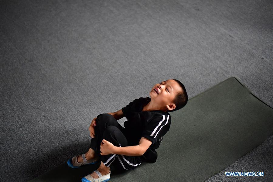 A trainee does a somersault excercise at an acrobatics school in Dongbeizhuang Village of Puyang, central China\'s Henan Province, July 11, 2018. In Dongbeizhuang Village, an acrobatics school enrols some 40 trainees aged between five and 15 who are faced with financial difficulties. The school offers both skills trainings and academic lessons but charges no tuition fees, preparing the trainees to join larger troupes with greater opportunities. (Xinhua/Feng Dapeng)