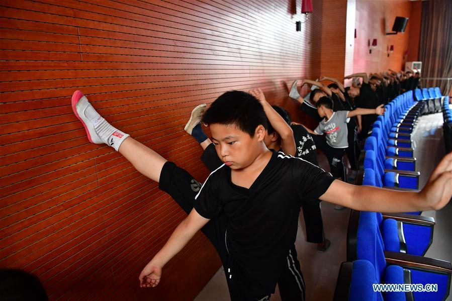 Trainees do warm-up excercises at an acrobatics school in Dongbeizhuang Village of Puyang, central China\'s Henan Province, July 11, 2018. In Dongbeizhuang Village, an acrobatics school enrols some 40 trainees aged between five and 15 who are faced with financial difficulties. The school offers both skills trainings and academic lessons but charges no tuition fees, preparing the trainees to join larger troupes with greater opportunities. (Xinhua/Feng Dapeng)