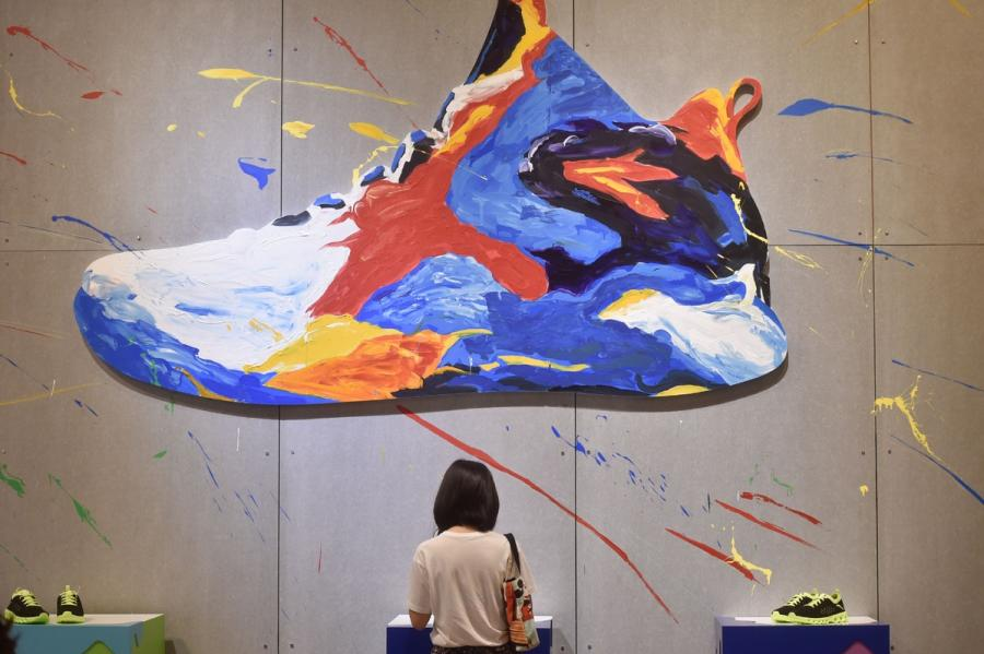 A potential client studies Anta sneakers during an annual expo for the shoes and sports industry in Jinjiang, Fujian Province on April 18, 2017. (Photo/Xinhua)