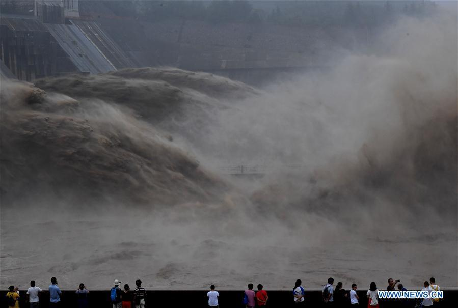 Tourists watch water gushing out from the Xiaolangdi Reservoir on the Yellow River in central China\'s Henan Province, July 11, 2018. (Xinhua/Li Jianan)