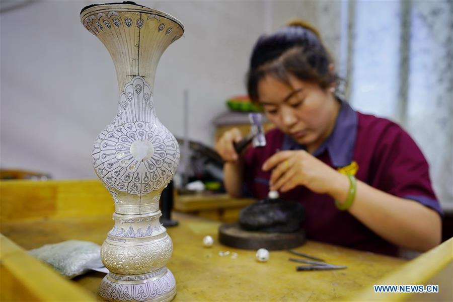 A worker makes a silverware at a workshop in Malanyu Township in Zunhua City, north China\'s Hebei Province, July 11, 2018. Gold and silver processing in Malanyu Township has a long history and the industry is expanding as craftsmen blend modern elements with traditional techniques in recent years. To date, there are more than 80 enterprises that provide over 2,000 jobs for local residents. (Xinhua/Mu Yu)