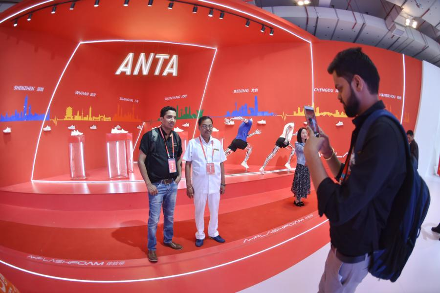 ndian businessmen pose for a photo at the Anta booth during an annual expo for the shoes and sports industry in Jinjiang, Fujian Province on April 19, 2018. (Photo/Xinhua)